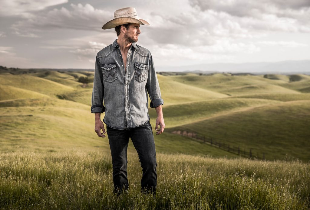 Standing in Front of an Open Western Plain, the Man in this Portrait is Wearing Work Clothes, Cowboy Boots and Hat.