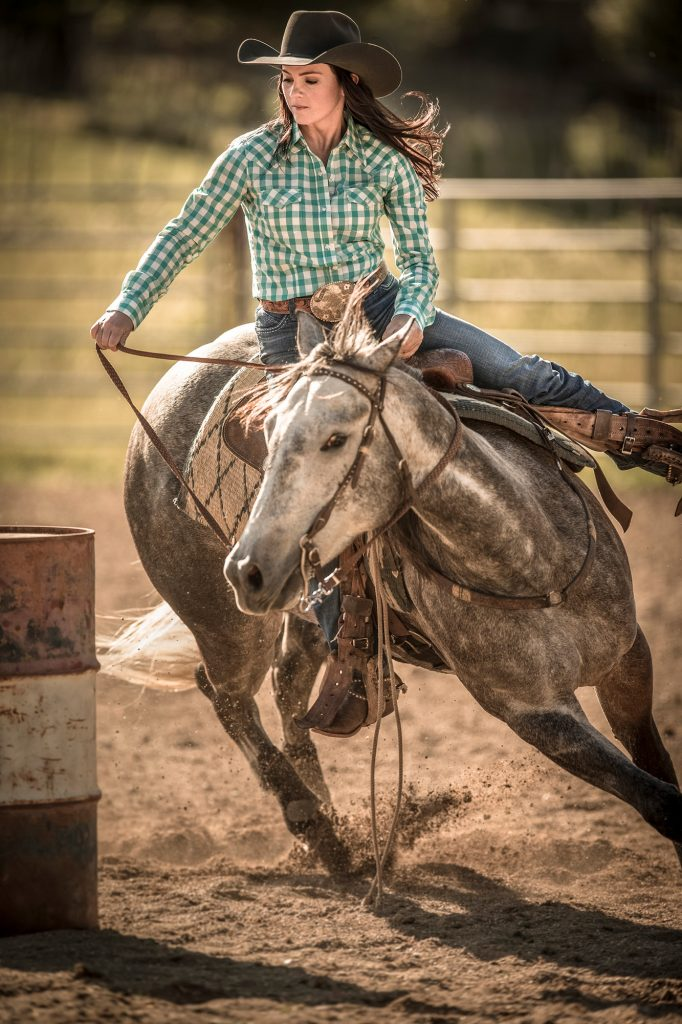 Western Photographer, Tyler Stableford, Captures this Incredible Action Shot of a Modern Cowgirl Barrel Racing at a Rodeo.