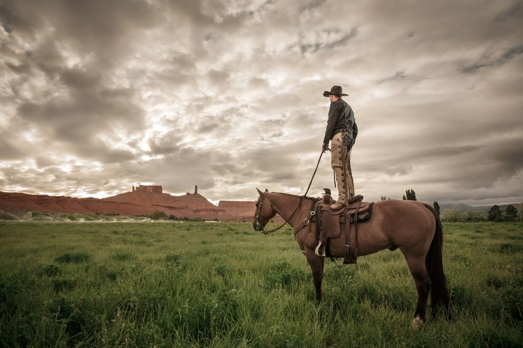 Standing on His Saddle in Castle Valley, Utah, a Modern Cowboy in Western Outfit Creates a Dramatic Picture. Looking West, he is an Iconic Image.