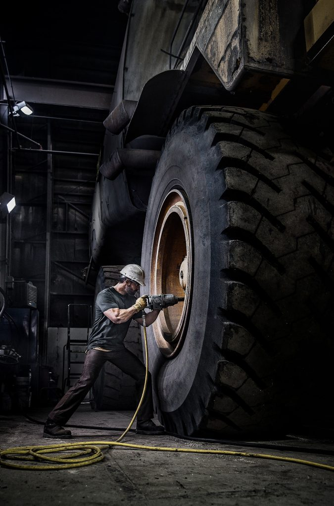 This Photograph Shows a Mine Worker Repairing One of the World's Largest Dumptruck. American Industry is Displayed in this Stark Image.