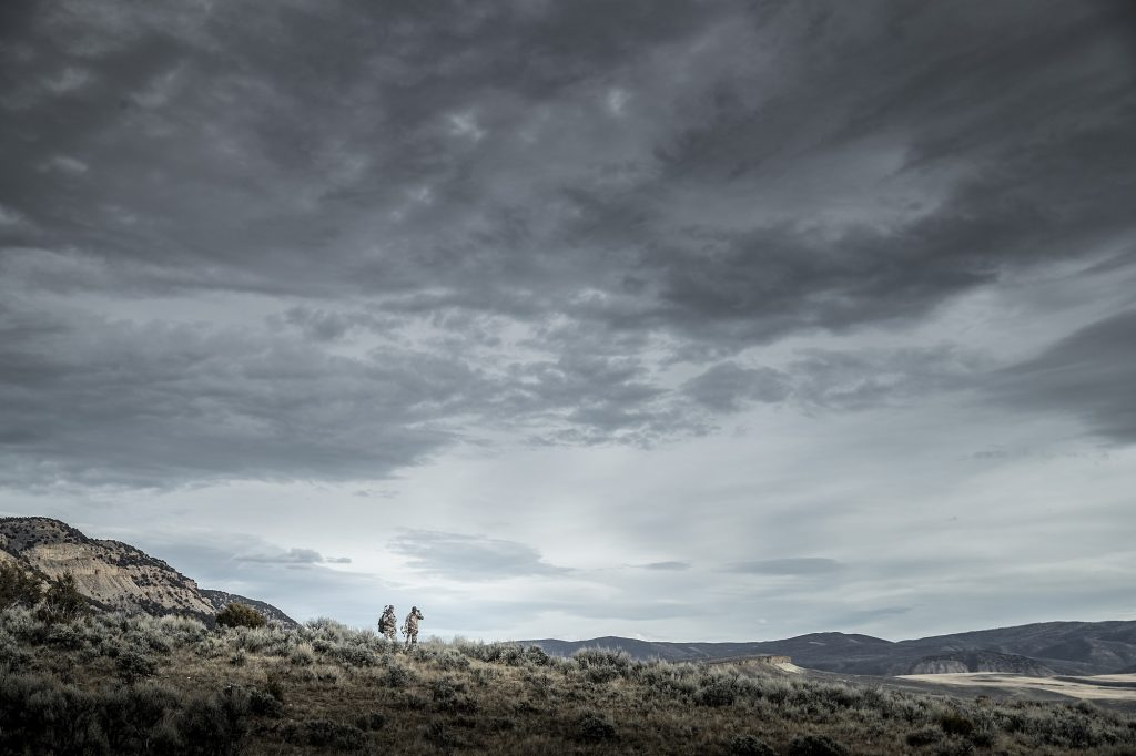 In the Vast Expanse of Sage Brush and Grasses, Two Hunters Search for their Quarry in this Stark Photograph.