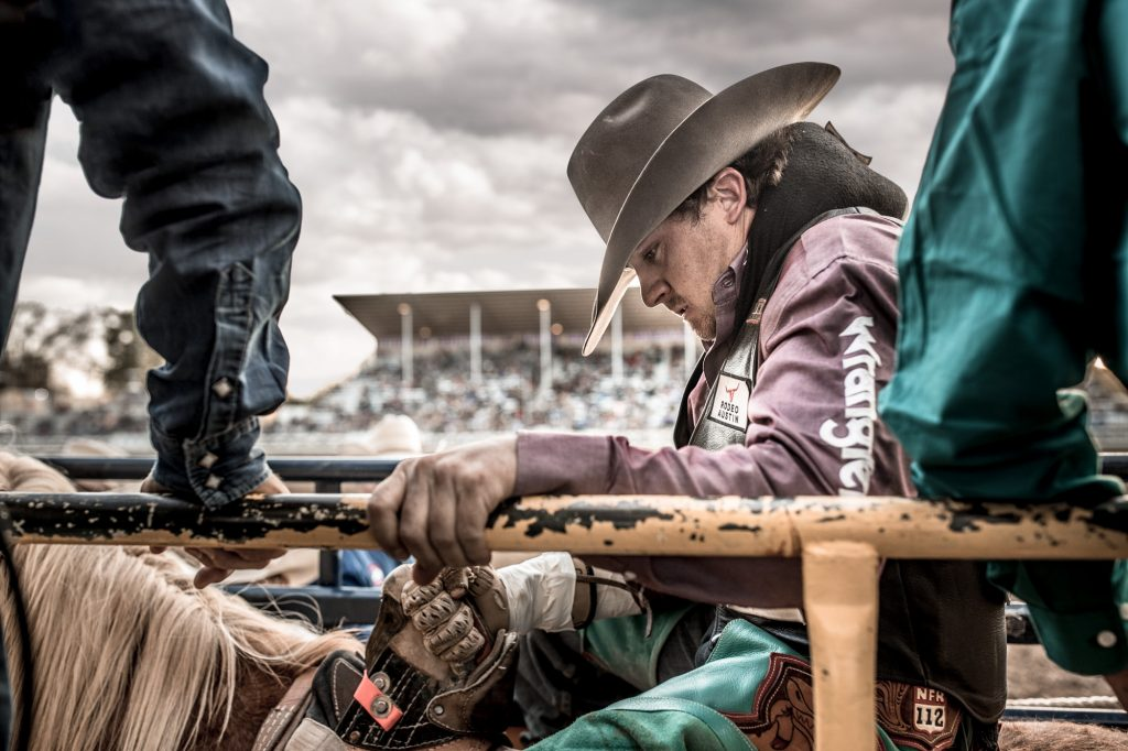 This Professional Cowboy Holds on the Railing in the Pen, Waiting for his Turn on a Bucking Bronco, His Eyes are Focused and Intent.