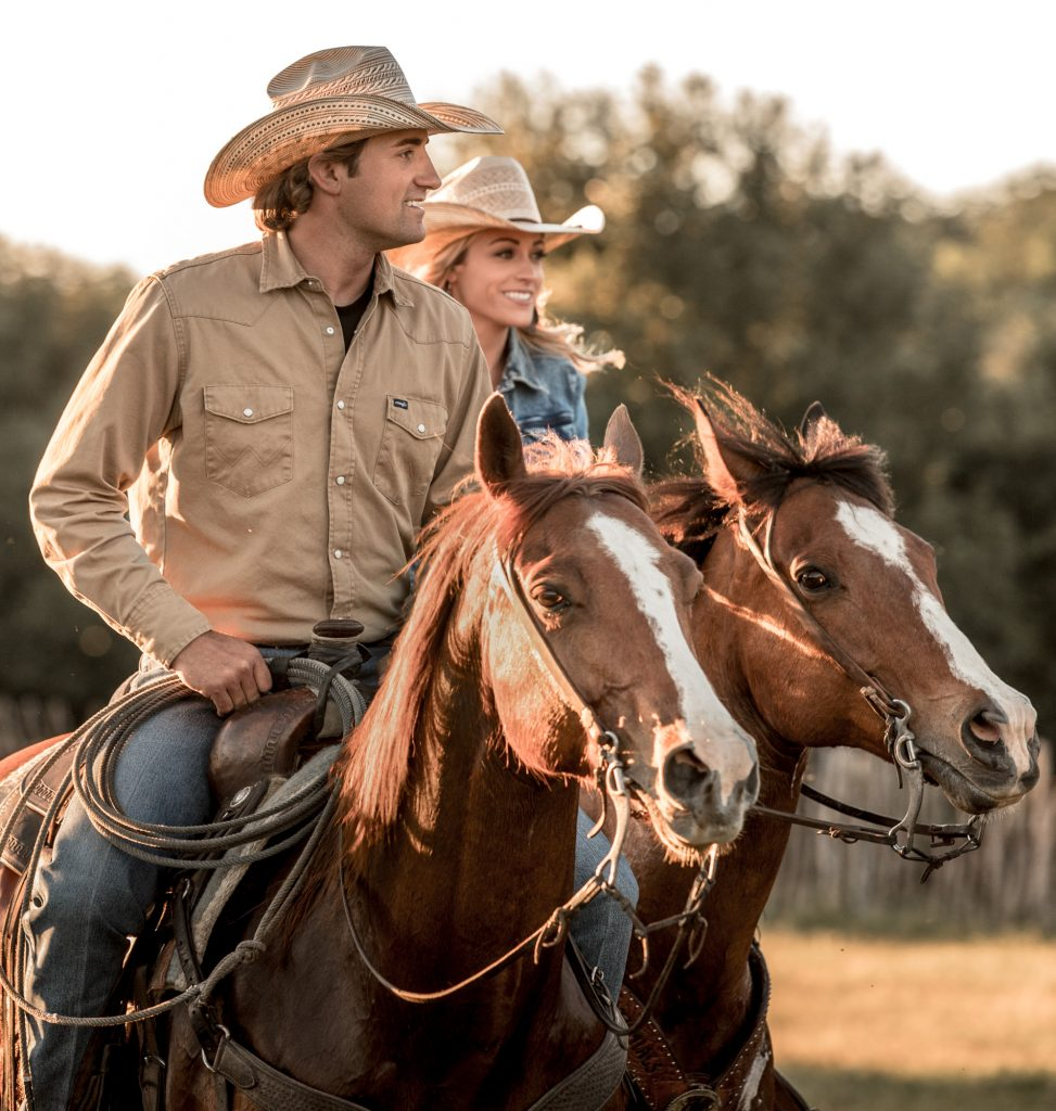 A Man and Woman in Western Style Clothing go Horseback Riding Together In the Evening.