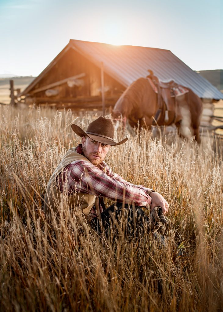 This Dramatic Image of a Modern Cowboy at Sunset is a Picture of Life in the West. His Horse Grazes Quietly Near a Barn in the Tall Grass.