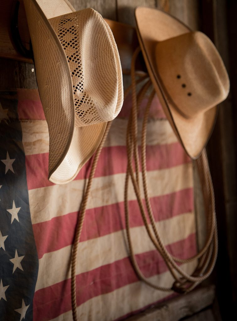 Cowboy Hats, a Lariat, and an American Flag are Symbols of Western Americana. Portraits Like These are Captured in Series about Modern Cowboys.
