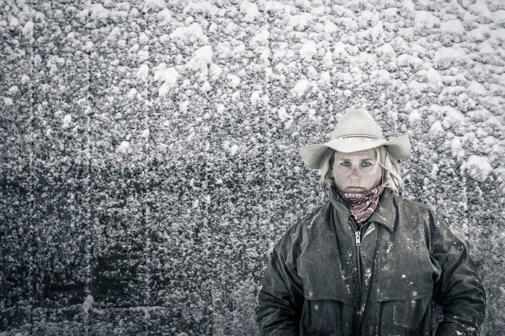 Standing in a Blizzard on Her Colorado Ranch, a Woman Poses in her Work Coat for Director/Photographer Tyler Stableford.