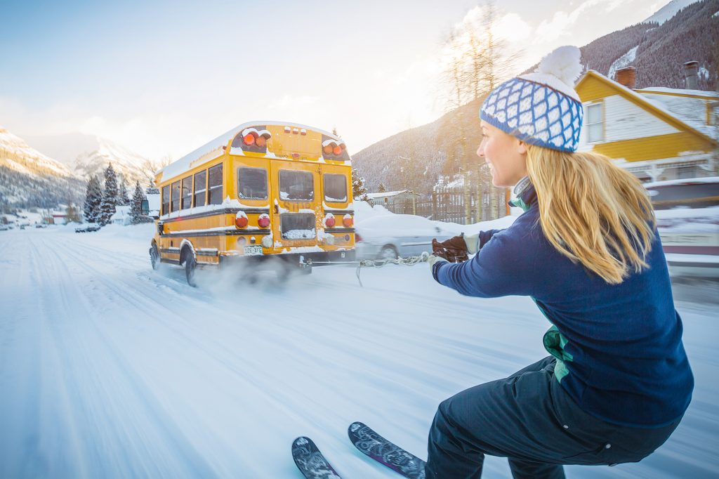 Mountain Life has Many Quirky Traditions Like Skiing While Being Towed by a School Bus. Taken in Silverton, Colorado, this Photo of a Woman Attempting that Feat is a Perfect Example of this Lifestyle.