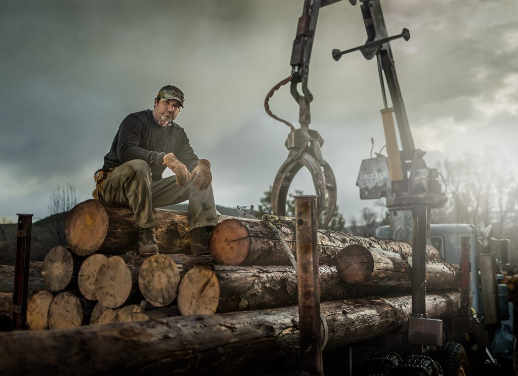 American Logging Worker Rests on Fresh-cut Boles. Heavy Duty Workwear Brands Like CAT Ford Cabela's Timberland and Ariat Are an Essential Part of this Industry.