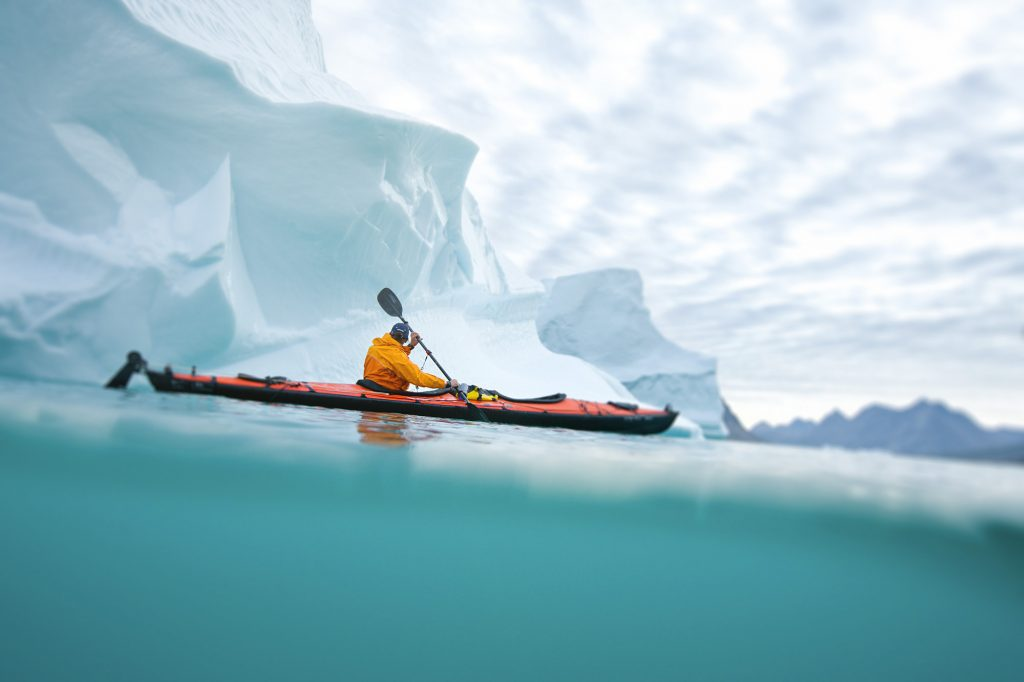 Overseas Adventure Photographer Photographed a Sea Kayaker in Icy Waters near a Tasilaq, Greenland. Blue Water, Fjords, and a Gray Sky Make Dramatic Backdrop.