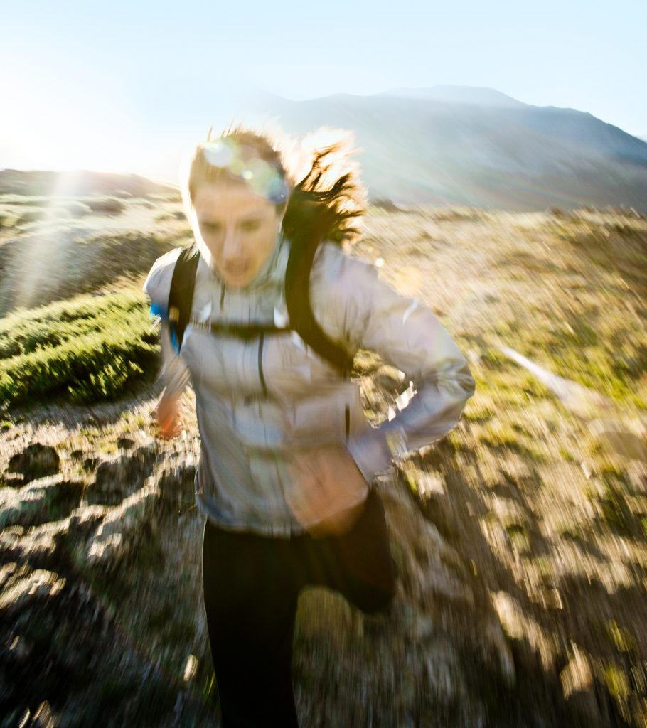 Action Shot of a Female Athlete Trail Running the Rocky Mountains. Award Winning Adventure Photographer Captures this Moment of Active Lifestyle.
