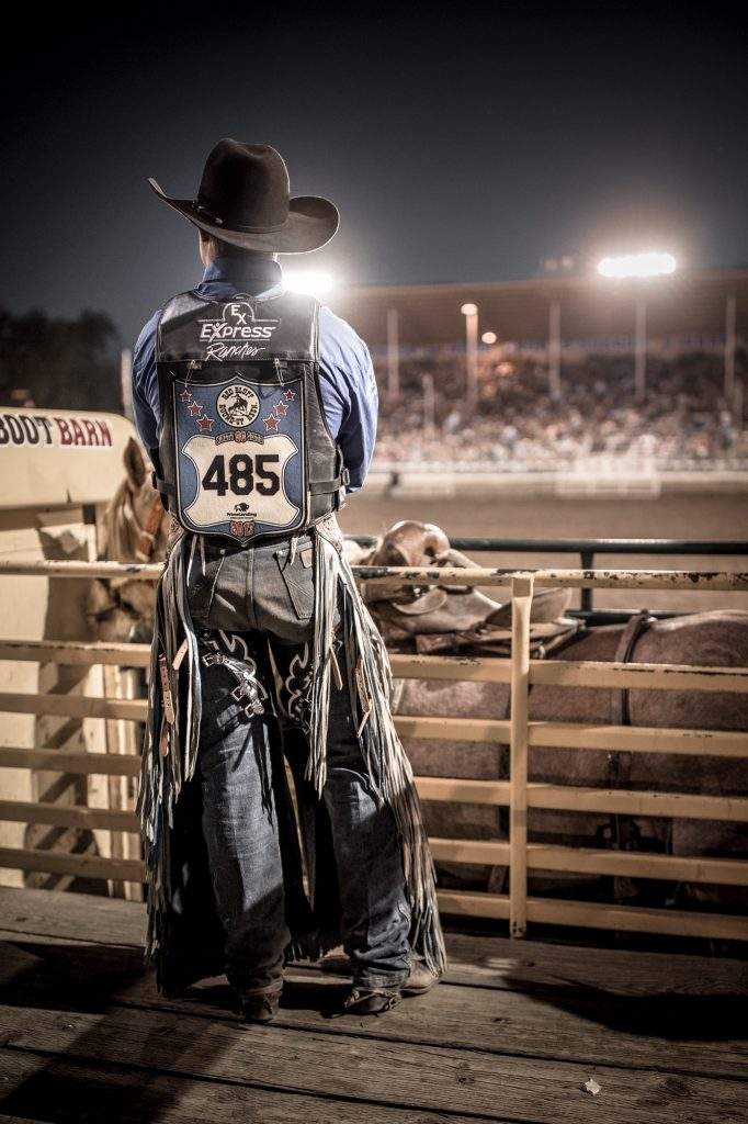 Black Cowboy Hat, Chaps, Cowboy Boots, Spurs, Jeans and Denim Clothing are Worn by a Cowboy Waiting for His Turn at a Bronc Riding Event.
