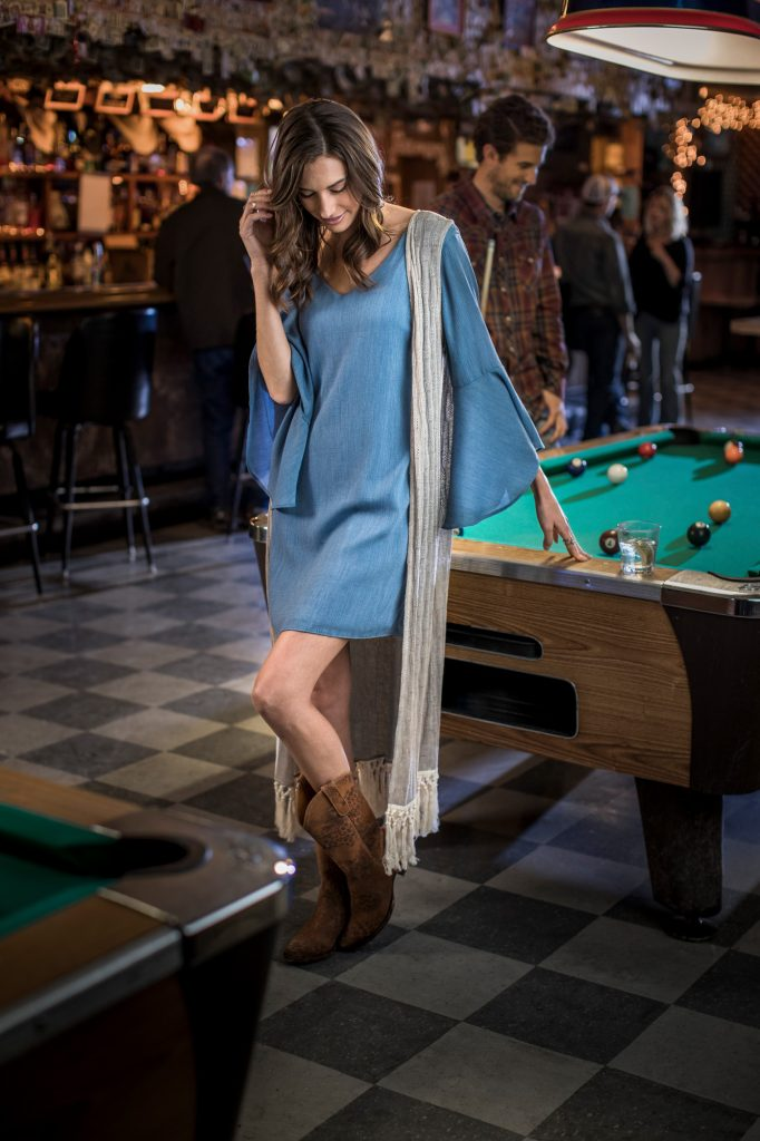 Leaning on a Pool Table in a Western Style Bar, this Woman in Cowboy Boots and Casual Western Apparel Highlights a Friday Night in American West.