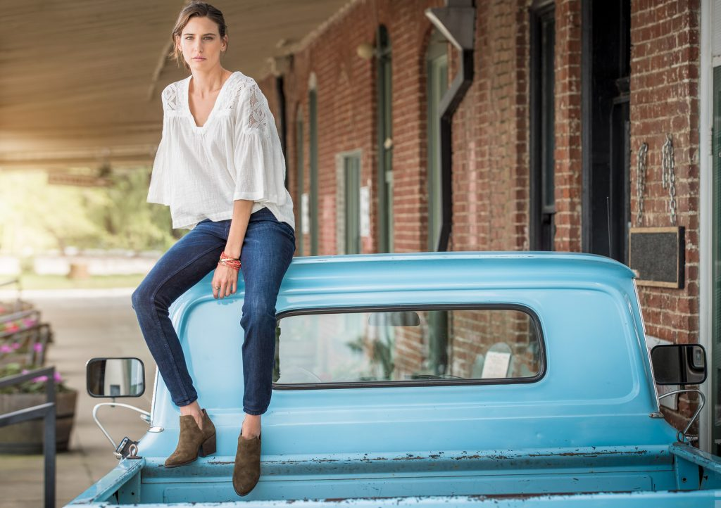 The Young Female Model in this Image Poses Casually on the Top of a Vintage Truck Beside a Brick and Mortar Wall.