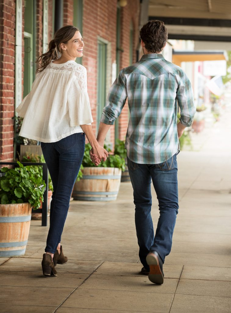 This Couple Walks Hand in Hand Down the Sidewalk of Small Town Mainstreet in Wrangler Brand Casual Apparel.